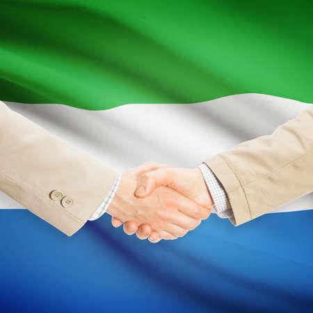 sierra leone: Businessmen shaking hands with flag on background - Sierra Leone