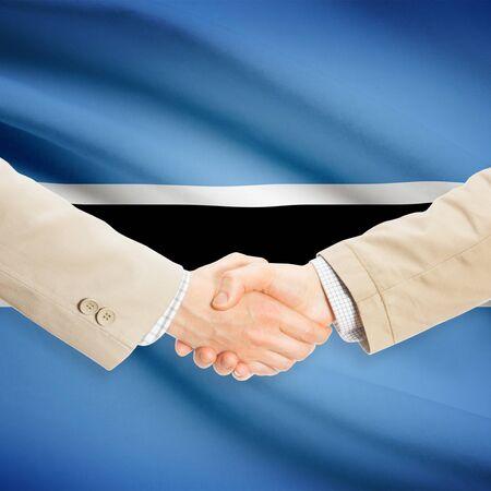 botswanan: Businessmen shaking hands with flag on background - Botswana