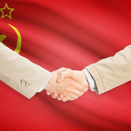 the ussr: Businessmen shaking hands with flag on background - USSR - Soviet Union