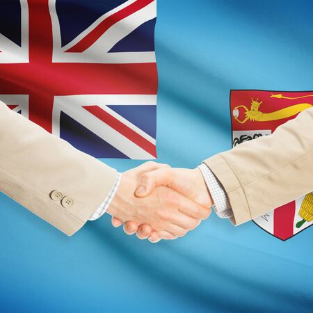 fijian: Businessmen shaking hands with flag on background - Fiji Stock Photo