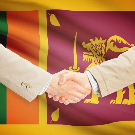 sri lankan flag: Businessmen shaking hands with flag on background - Sri Lanka