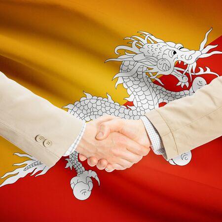 Businessmen shaking hands with flag on background - Bhutan Stock fotó