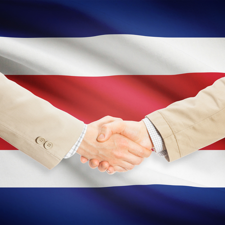 costa rican flag: Businessmen shaking hands with flag on background - Costa Rica