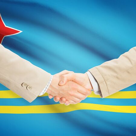 Businessmen shaking hands with flag on background - Aruba