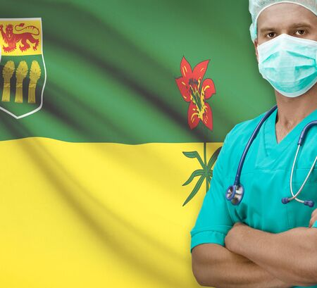 saskatchewan flag: Surgeon with Canadian province flag on background - Saskatchewan Stock Photo