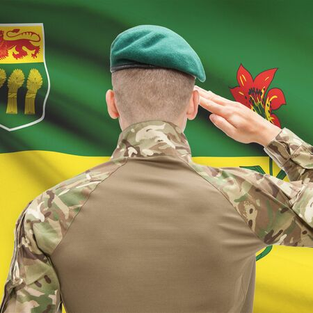 saskatchewan flag: Soldier saluting to Canadial province flag series - Saskatchewan