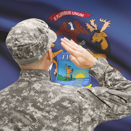 michigan flag: Soldier saluting to USA state flag conceptual series - Michigan