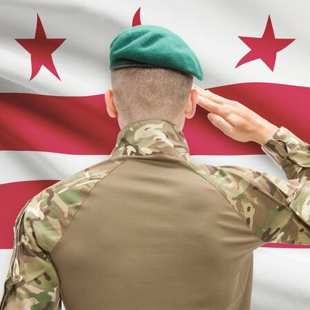 district of columbia: Soldier saluting to US state flag series - District of Columbia Stock Photo