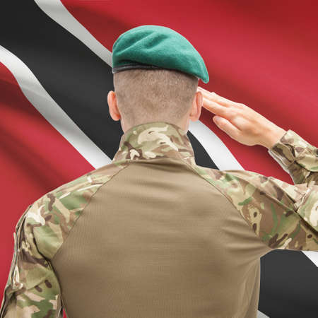 national flag trinidad and tobago: Soldier in hat facing national flag series - Trinidad and Tobago Stock Photo
