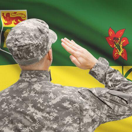 saskatchewan flag: Soldier saluting to Canadial province flag conceptual series - Saskatchewan