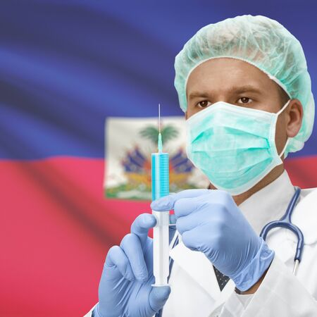 Doctor with syringe in hands and flag on background series - Haiti Фото со стока