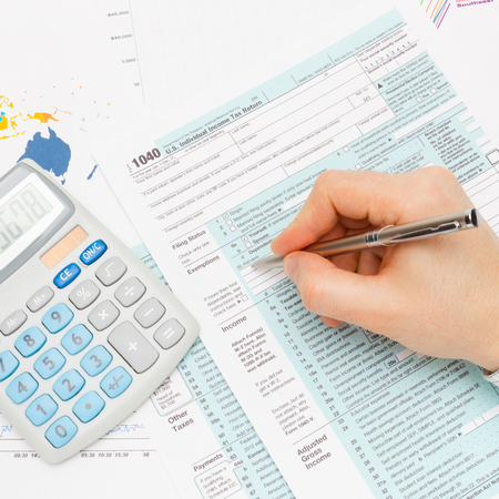 taxable income: Male filling out 1040 US Tax Form with silver pen - studio shot Stock Photo