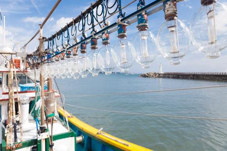 Squid fishing boat entering port Stock Photo