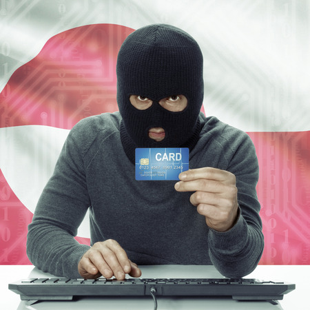 greenlandic: Dark-skinned hacker with credit card in hand and flag on background - Greenland Stock Photo