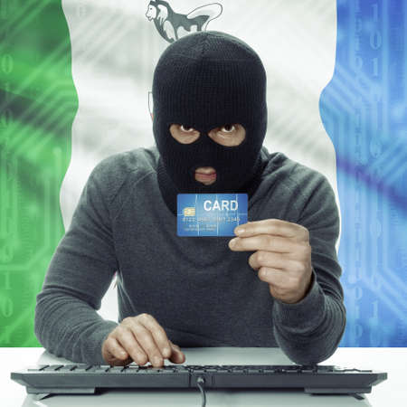 yukon: Dark-skinned hacker holding credit card with Canadian province flag on background - Yukon