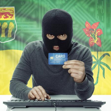 saskatchewan flag: Dark-skinned hacker holding credit card with Canadian province flag on background - Saskatchewan