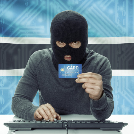 botswanan: Dark-skinned hacker with credit card in hand and flag on background - Botswana Stock Photo