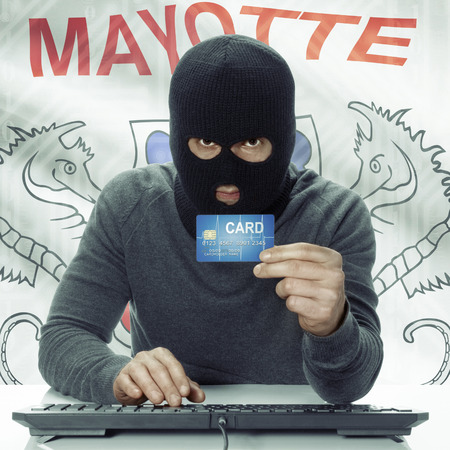 mayotte: Dark-skinned hacker with credit card in hand and flag on background - Mayotte