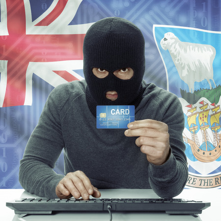 falkland: Dark-skinned hacker with credit card in hand and flag on background - Falkland Islands
