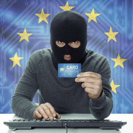 credit union: Dark-skinned hacker with credit card in hand and flag on background - EU - European Union Stock Photo