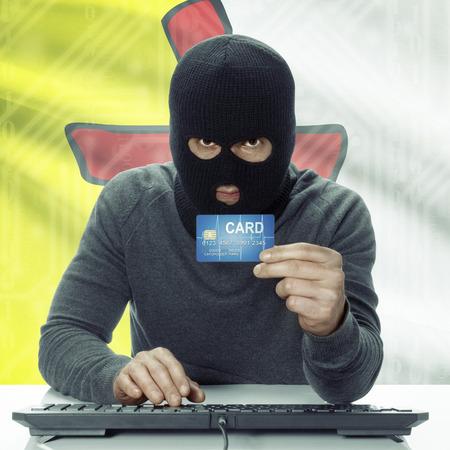 money risk: Dark-skinned hacker holding credit card with Canadian province flag on background - Nunavut