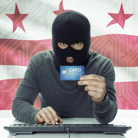 district of colombia: Dark-skinned hacker with credit card in hand and USA states flag on background - District of Columbia Archivio Fotografico