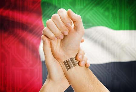 united arab emirates: Barcode ID number on wrist of a human and national flag on background - United Arab Emirates Stock Photo