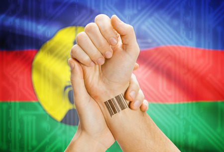 new caledonia: Barcode ID number on wrist of a human and national flag on background - New Caledonia