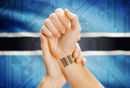 botswanan: Barcode ID number on wrist of a human and national flag on background - Botswana Stock Photo