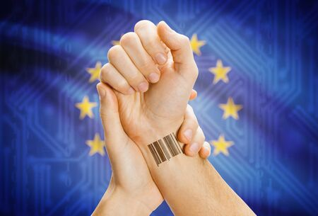 Barcode ID number on wrist of a human and national flag on background - European Union Stock Photo