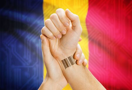 chadian: Barcode ID number on wrist of a human and national flag on background - Chad