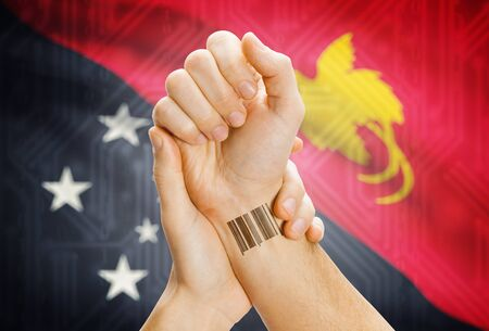 papua new guinea: Barcode ID number on wrist of a human and national flag on background - Papua New Guinea