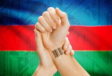 azeri: Barcode ID number on wrist of a human and national flag on background - Azerbaijan