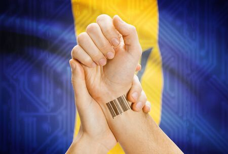 barbadian: Barcode ID number on wrist of a human and national flag on background - Barbados