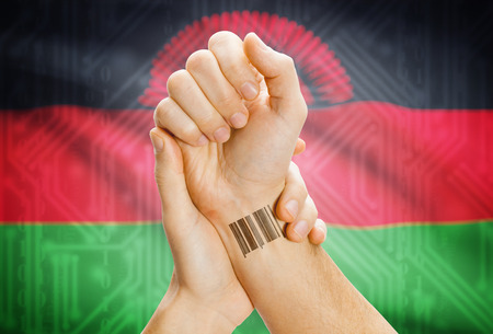 malawian: Barcode ID number on wrist of a human and national flag on background - Malawi Stock Photo