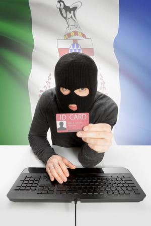 yukon: Hacker with ID card in hand and Canadian province flag on background - Yukon Stock Photo
