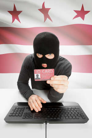district of columbia: Hacker with ID card in hand and USA states flag on background - District of Columbia