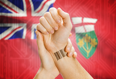 tatoo: Barcode ID number tatoo on wrist and Canadian province flag on background - Ontario