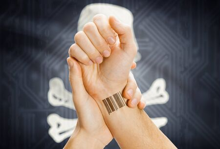 piracy: Barcode ID tattoo on hand and Jolly Roger flag on background - symbol of piracy Stock Photo