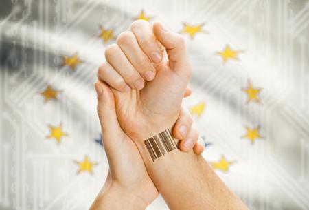 tatoo: Barcode ID number tatoo on wrist and USA statesl flag on background - Rhode Island