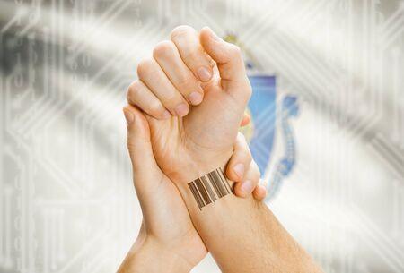 tatoo: Barcode ID number tatoo on wrist and USA statesl flag on background - Massachusetts Stock Photo