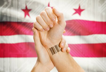 district of colombia: Barcode ID number tatoo on wrist and USA statesl flag on background - District of Columbia Archivio Fotografico