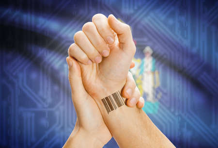 tatoo: Barcode ID number tatoo on wrist and USA statesl flag on background - Maine