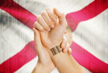 floridian: Barcode ID number tatoo on wrist and USA statesl flag on background - Florida Stock Photo