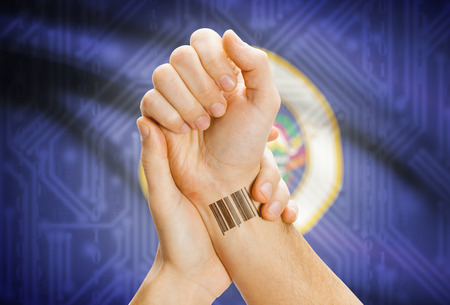 breaking the code: Barcode ID number tatoo on wrist and USA statesl flag on background - Minnesota