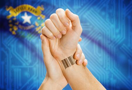 tatoo: Barcode ID number tatoo on wrist and USA statesl flag on background - Nevada