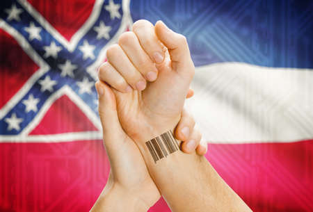 tatoo: Barcode ID number tatoo on wrist and USA statesl flag on background - Mississippi