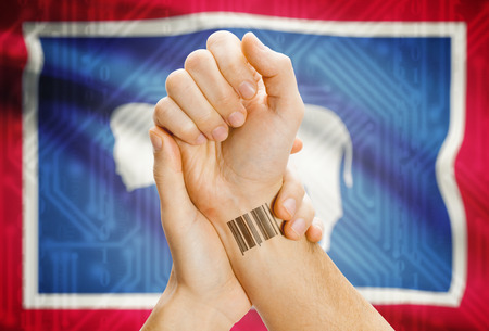 breaking the code: Barcode ID number tatoo on wrist and USA statesl flag on background - Wyoming