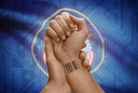 dark skinned: Barcode ID number tattoo on wrist of dark skinned person and USA states flag on background - Utah
