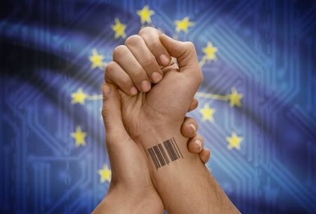 dark skinned: Barcode ID number tattoo on wrist of dark skinned person and USA states flag on background - Indiana Stock Photo